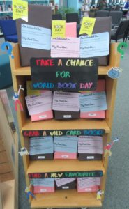 """Photograph of a small shelf book display. A poster on the shelf reads, """"Take A Chance for World Book Day"""". All of the books on the shelf are wrapped up in brown or pink paper, and have a small cryptic label (unreadable in the photo) stuck to them. End description."""