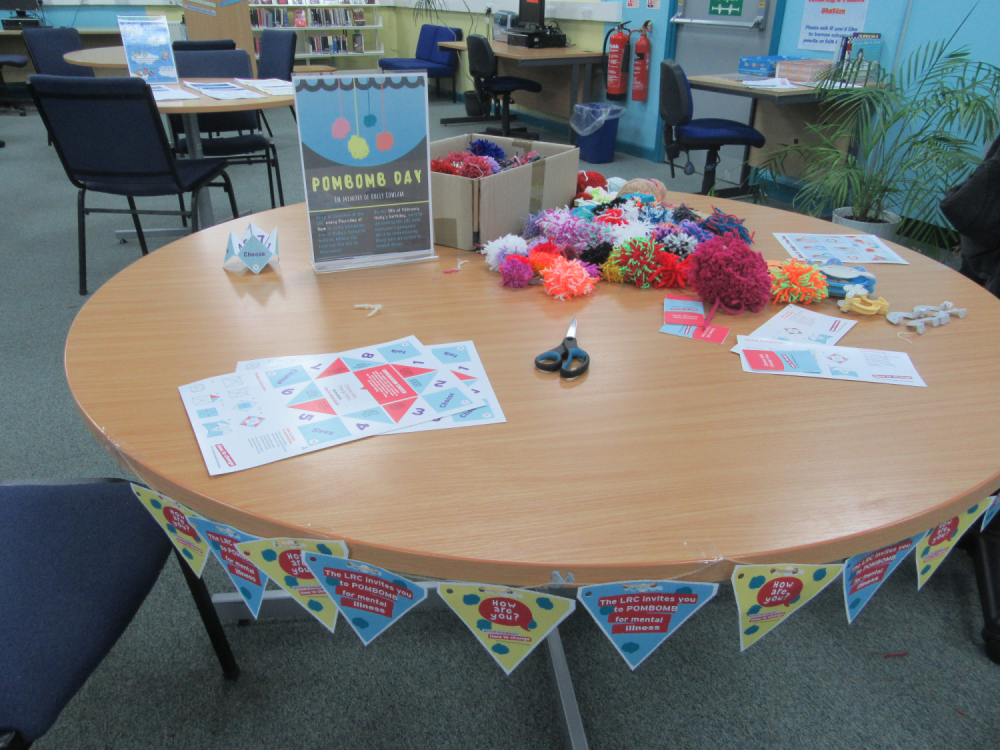 [Image Description: Table in Filton LRC with pompoms and informational posters.]