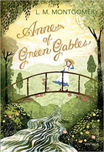 [Image Description: Book cover for Anne of Green Gables. A young girl with red hair stands on a bridge over a stream, in a green wood.]