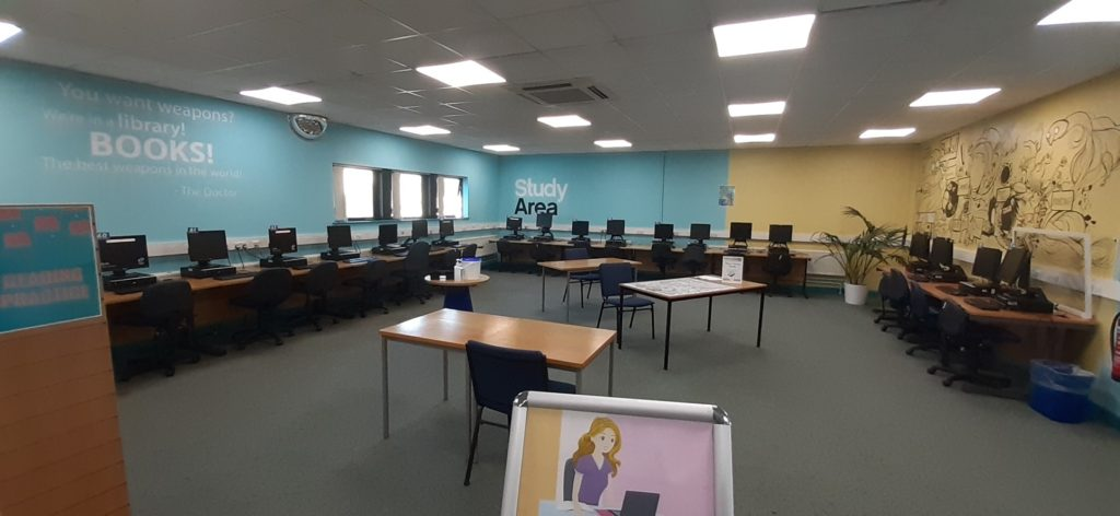 """Photograph of the Quiet Study Area at LibraryPlus+ Filton. The photograph shows a room with grey carpet and three windows along the right wall. The walls are sky-blue on the right, and pastel yellow on the left. Around the walls are desks with computers. At jaunty angles in the middle of the room are three single-occupancy desks. On the far back wall, to the right, are black and white vinyl stickers which read """"Study Area"""". To the front right on the wall are more vinyl stickers with white text, but these are unreadable in this image other than the large word """"BOOKS!"""""""