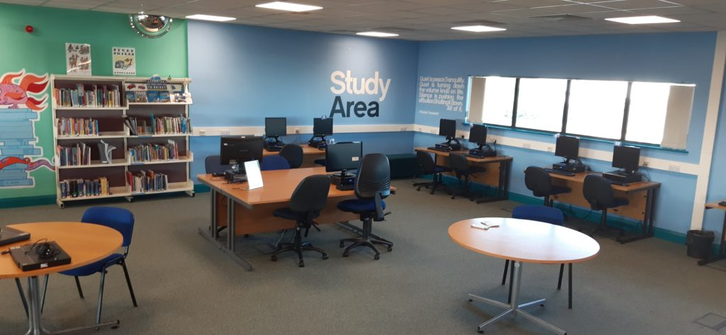 """A photograph of one corner of the Group Study Area room at LibraryPlus+ Filton. Grey carpet and four windows along the left wall. The walls are mostly blue, but a portion of wall on the right side is mint green, and a small part of a mural is visible, cut off by the edge of the phot. Along the far walls are three desks with six computers, and a low soft bench. In the middle of the photo is a large group desk with two computers, one on each side of the large desk, and four chairs. There is also a large round table with a a chair. To the far left, cut off by the edge of the photograph, there is another round table with a chair. To the left of the back wall, before the mural, are two bays of bookshelves filled with books. On the wall, near the corner, are black and white vinyl stickers which read """"Study Area"""". Next to this on the other side of the corner is some more text in vinyl stickers, but this is too small to read on this photograph. End of Image description."""